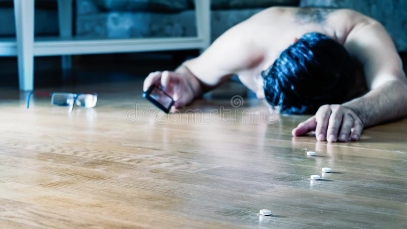 Man calling for help lying with pills on the floor. stock images