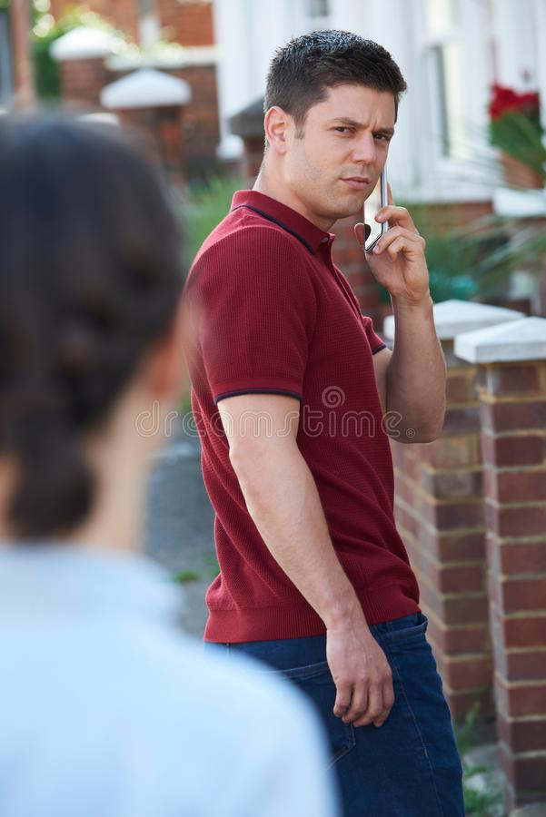 Man Calling For Help On Mobile Phone Whilst Being Stalked On Cit stock image