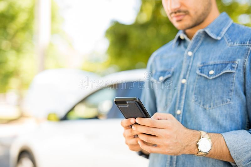 Man calling roadside assistance. Close up of man hands using phone with broken car in background. Man calling roadside assistance for his breakdown car stock image