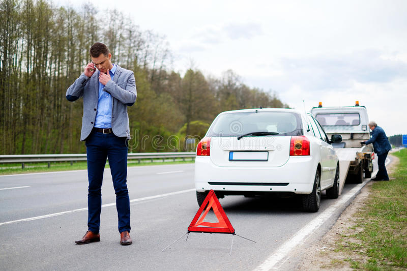 Man calling while tow truck picking up his broken car royalty free stock photography