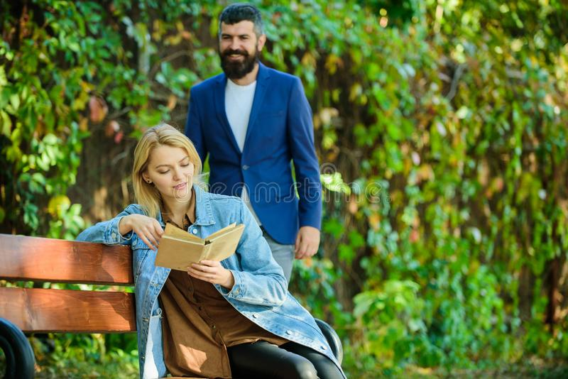 Man came to girlfriend on date. Girl sit bench read book while wait boyfriend. Romantic relations concept. Romantic date royalty free stock photo