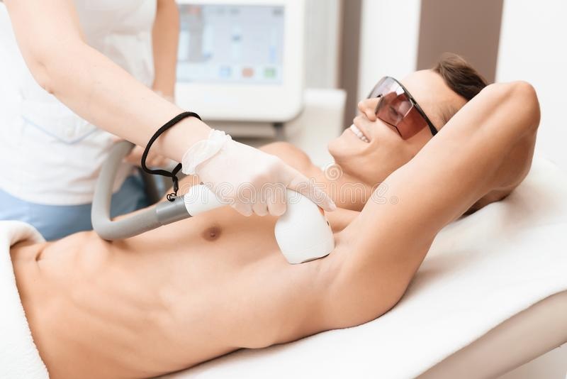 The man came to the procedure of laser hair removal. The doctor treats his armpit with a special apparatus. The man has red glasses stock images