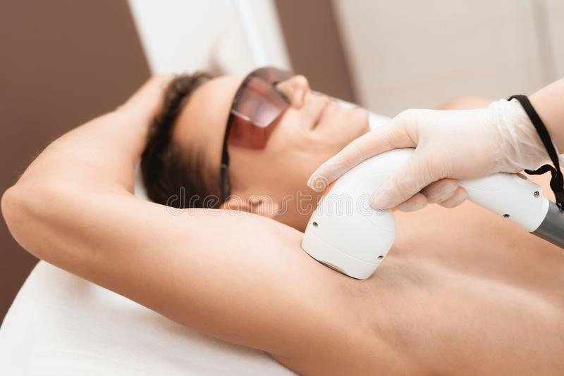 The man came to the procedure of laser hair removal. The doctor treats his armpit with a special apparatus. The man has red glasses stock photos