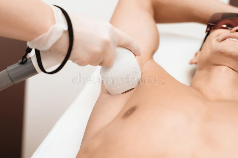 The man came to the procedure of laser hair removal. The doctor treats his armpit with a special apparatus. The man has red glasses stock photography