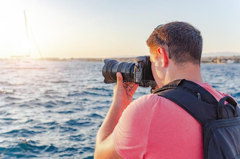 Man with a camera photographing the sunset on the sea coast. stock images