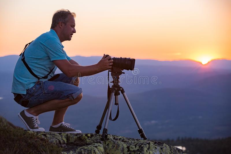 Man with camera and tripod filming sunset above mountain. stock photo