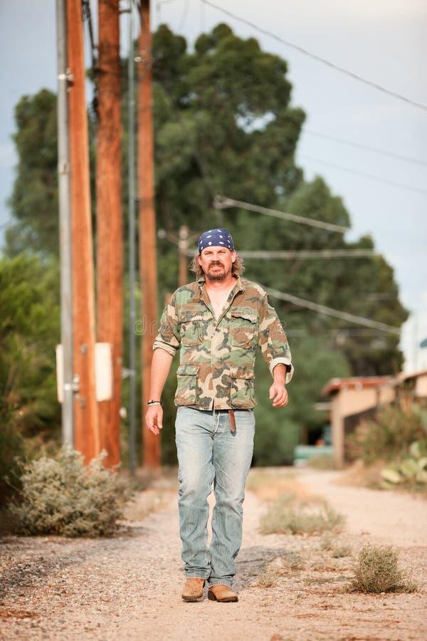 Man in camoflauge walking on dirt road. Rugged man in camoflauge walking on dirt road royalty free stock photos