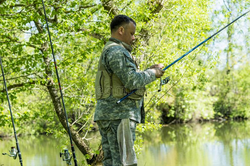A man in camouflage fishing rod on the river Bank in early summer royalty free stock image