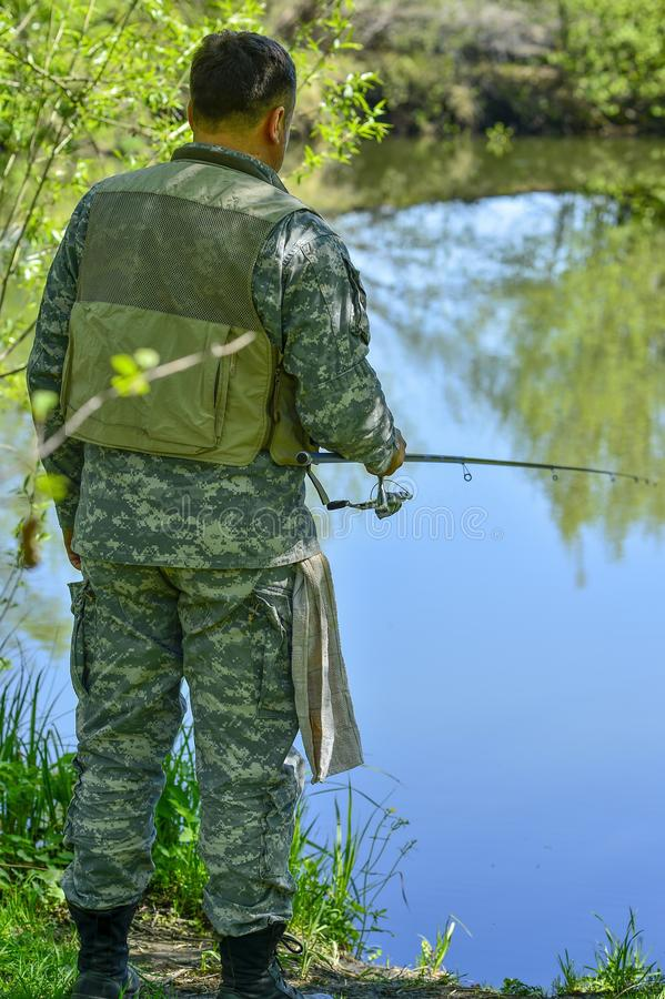 A man in camouflage fishing rod on the river Bank in early summer royalty free stock photo