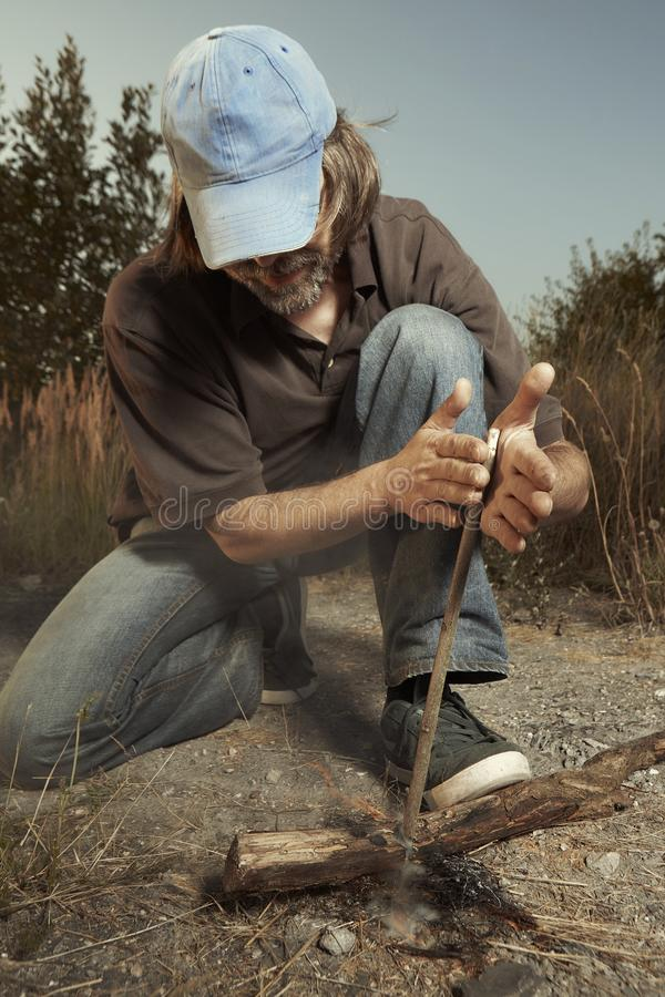 Free Man Camping In Nature Making Fire With Wood Stick Friction By Hands Royalty Free Stock Images - 121716389
