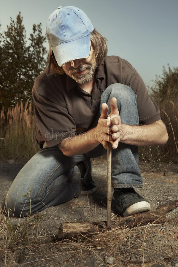 Man camping in nature making fire with wood stick friction by hands. Man in hat trying to make a fire with wood stick friction royalty free stock photo