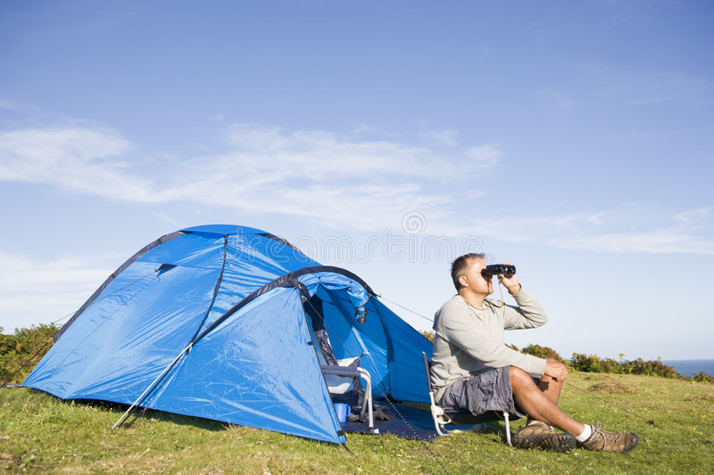 Man camping outdoors and looking through binocular royalty free stock images