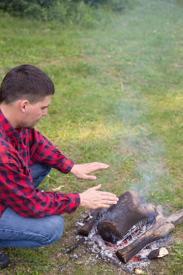 The man at the campsite with a campfire. The man at the campsite with a campfire in the summer forest stock images