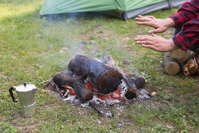 The man at the campsite with a campfire. The man at the campsite with a campfire in the summer forest royalty free stock photography