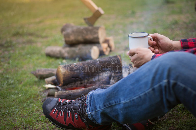 The man at the campsite with a campfire. The man at the campsite with a campfire in the summer forest stock photography
