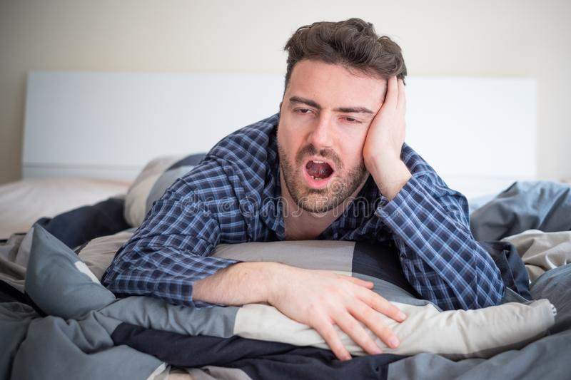 Man having problem sleeping in his bed stock images