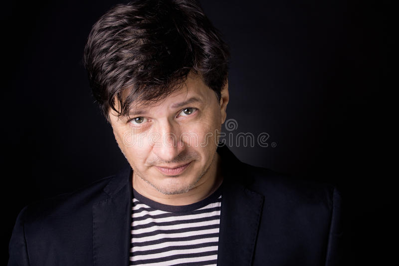 Man with candid look. Handsome man in his 40's looking in the camera with clear, candid eyes. Wearing T-shirt with stripes and a black jacket royalty free stock photos