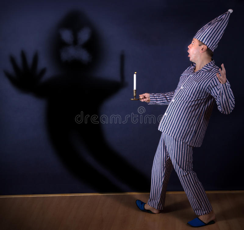 Man with candle. Frightened man with candle in pajamas royalty free stock images