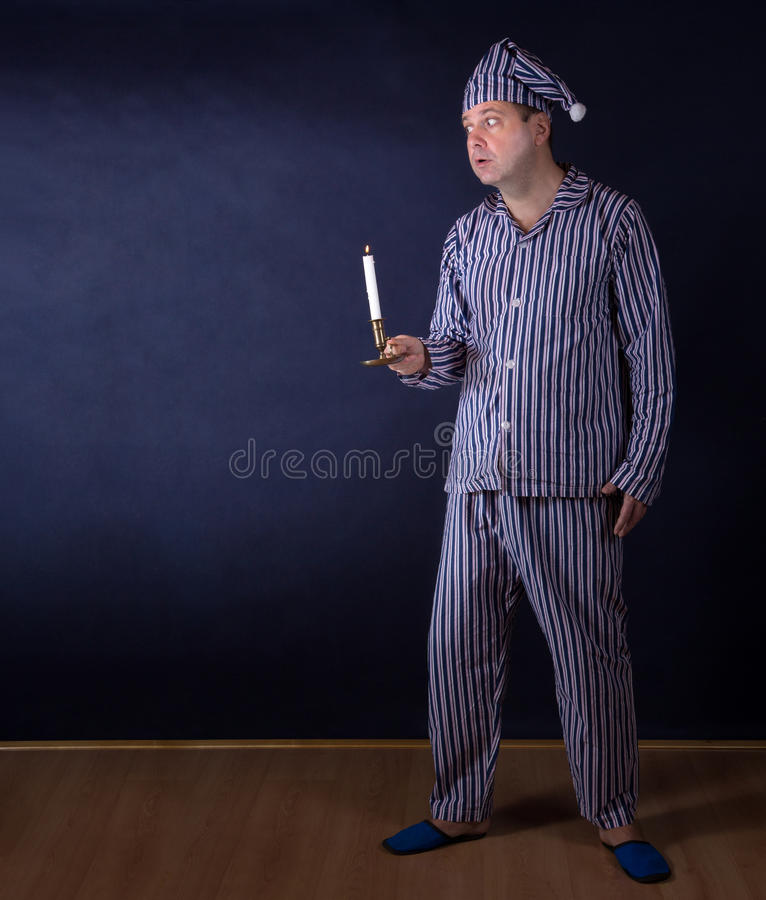 Man with candle in pajamas. Frightened man with candle in pajamas royalty free stock image
