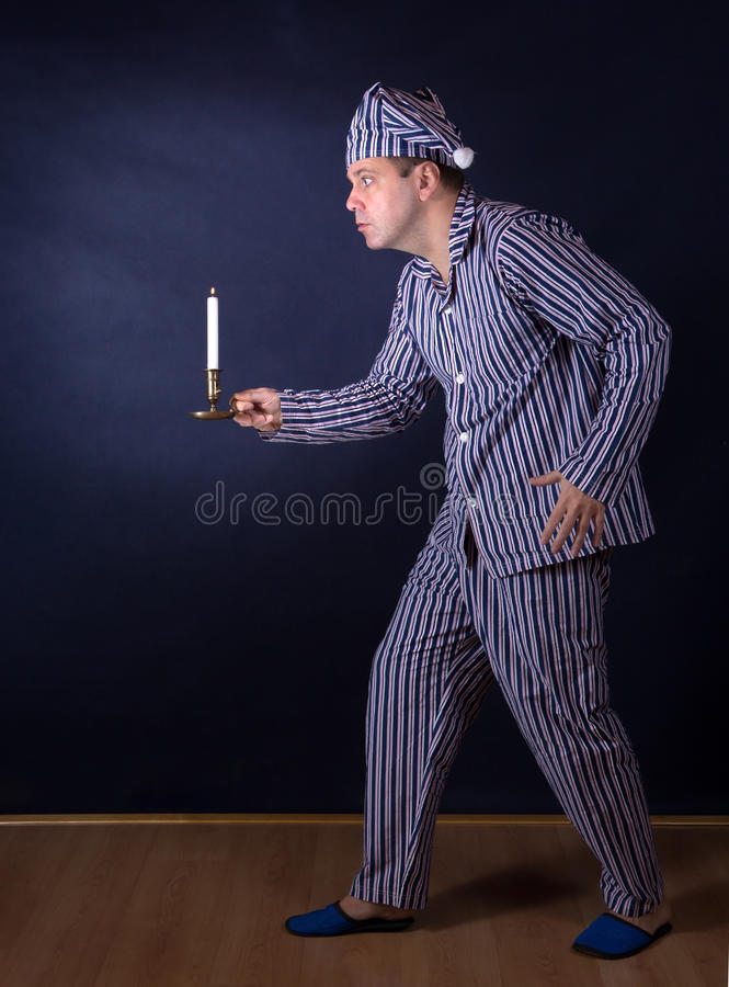 Man with candle in pajamas. Frightened man with candle in pajamas royalty free stock photography
