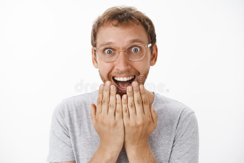 Man cannot hide happiness and excitement receiving awesome news holding palms above mouth smiling broadly with stock photo