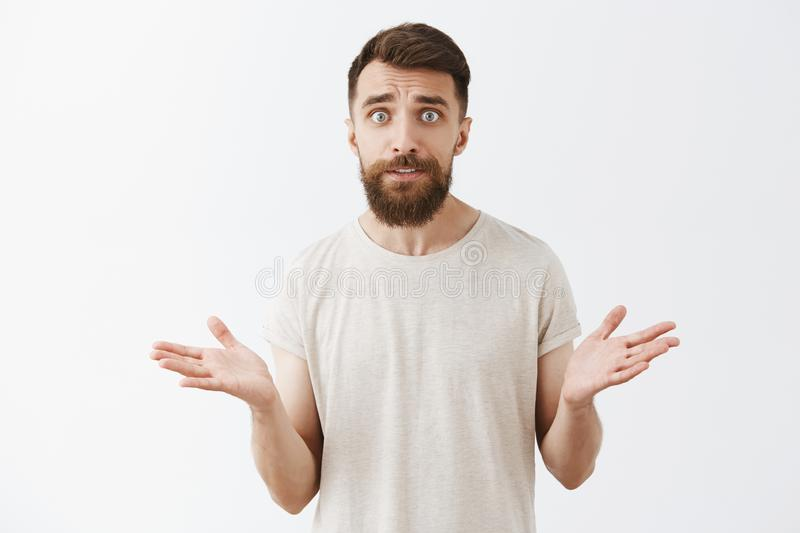Man cannot understand how wife spent all money. Confused concerned good-looking mature husband with long beard in casual stock photo