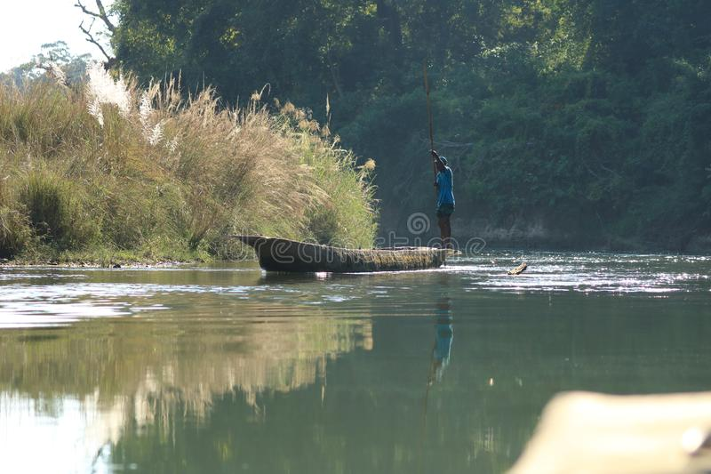 Man canoeing safari on wooden boat Pirogues on the Rapti river, in Chitwan National Park, Nepal royalty free stock image