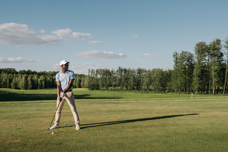Man in cap holding golf club and hitting ball on green lawn royalty free stock images