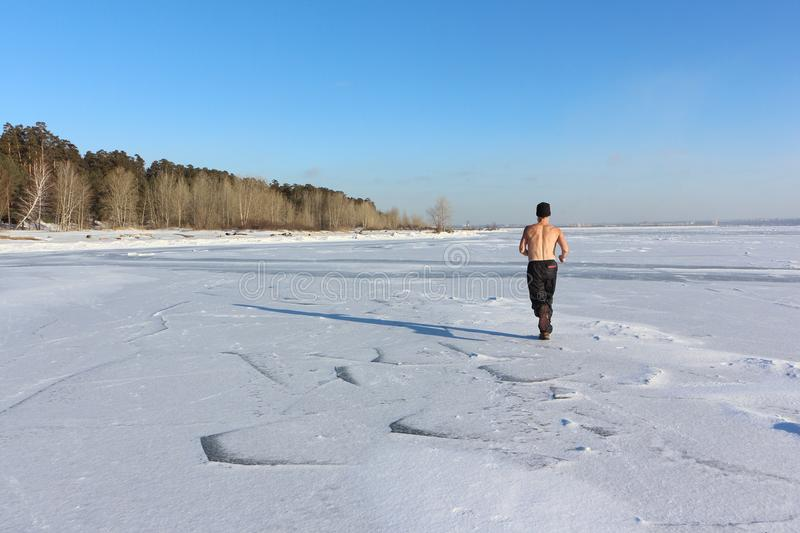 43f23ee47 Man In A Cap With A Naked Torso Running Across The Ice Of A Frozen ...