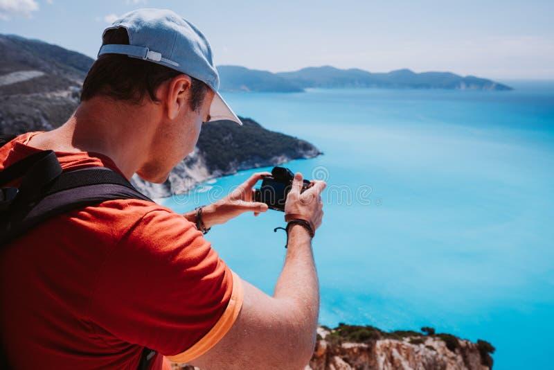 Man capture photograph of myrtos coastline sea landscape. Blue cyan water surface with island shape, Kefalonia, Greece stock images