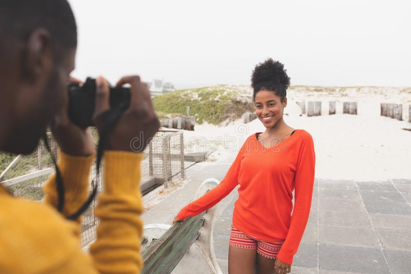 Man capturing photo of woman while standing at pavement. Rear view of African American man capturing photo of pretty Mixed-race woman while standing at pavement stock photos