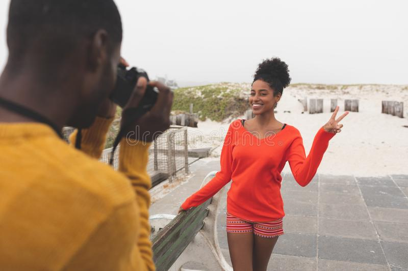 Man capturing photo of woman while standing at pavement. Rear view of African American men capturing photo of pretty Mixed-race women while standing at pavement royalty free stock photography