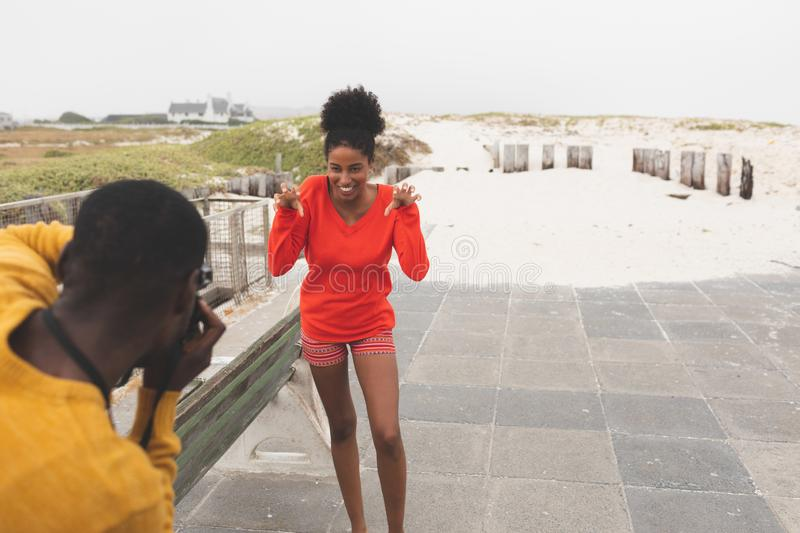 Man capturing photo of woman while standing at pavement. Rear view of handsome African American man capturing photo of beautiful Mixed-race woman while standing royalty free stock photo