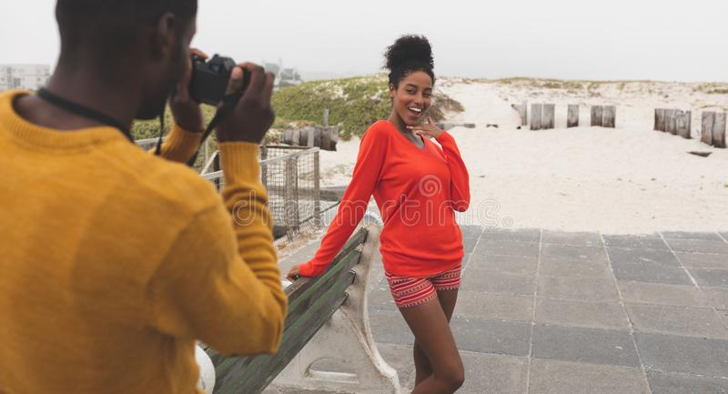 Man capturing photo of woman while standing at pavement. Rear view of handsome African American men capturing photo of pretty Mixed-race women while standing at royalty free stock photography