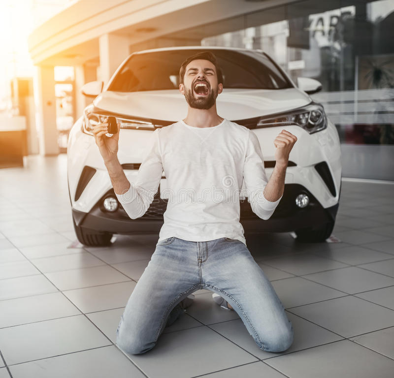 Man in car dealership. Yes, that& x27;s my new car! Customer in car dealership. Young man knelt down with keys in hand royalty free stock photo