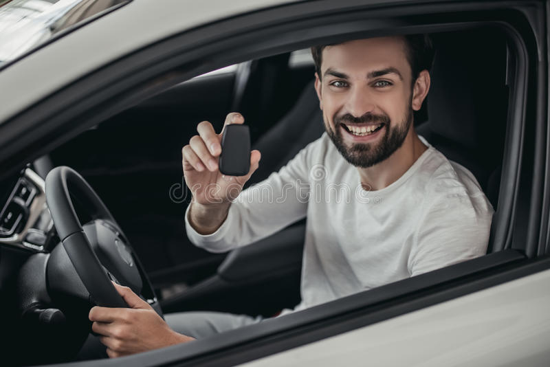 Man in car dealership. Young man is choosing a new vehicle in car dealership. Holding keys in hand, smiling and looking at the camera royalty free stock images