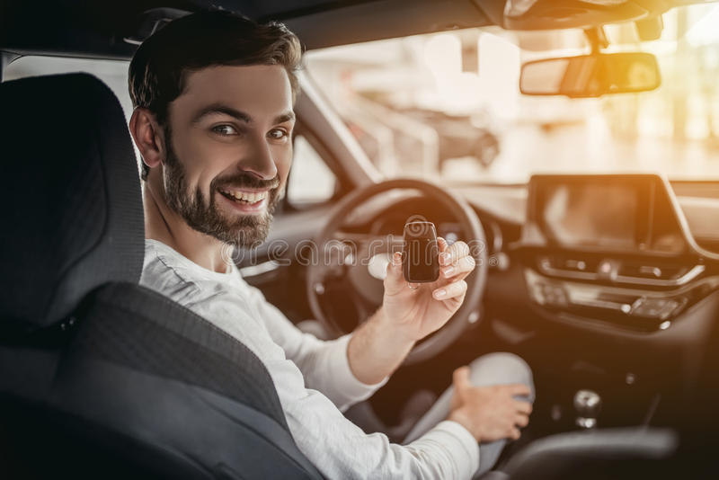Man in car dealership. Young man is choosing a new vehicle in car dealership. Holding keys in hand, smiling and looking at the camera stock photography