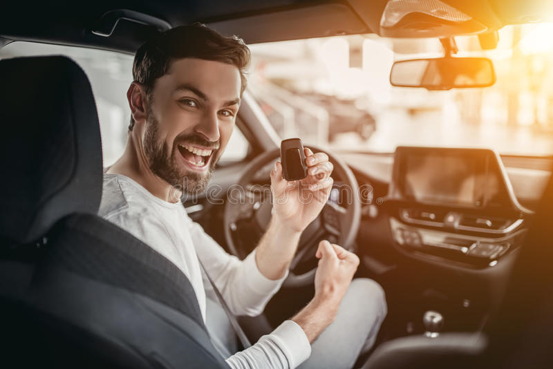 Man in car dealership. Young man is choosing a new vehicle in car dealership. Holding keys in hand, smiling and looking at the camera royalty free stock photography