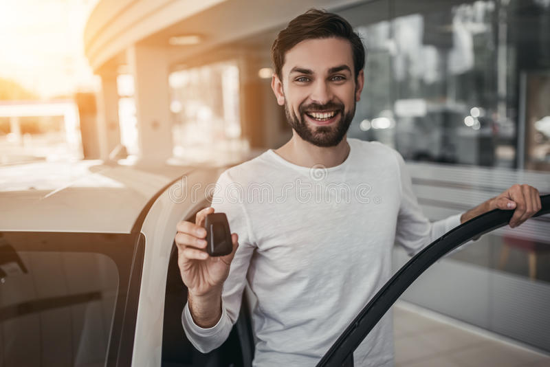 Man in car dealership. Young man is choosing a new vehicle in car dealership. Holding keys in hand, smiling and looking at the camera royalty free stock photos
