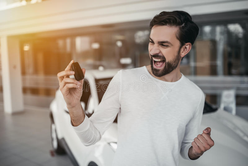 Man in car dealership. Young man is choosing a new vehicle in car dealership with keys in hand royalty free stock photography