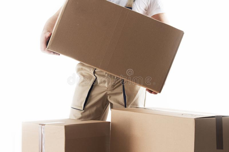 Man with cardboard box in hands. Relocation services. Mover with boxes. Loader. stock images