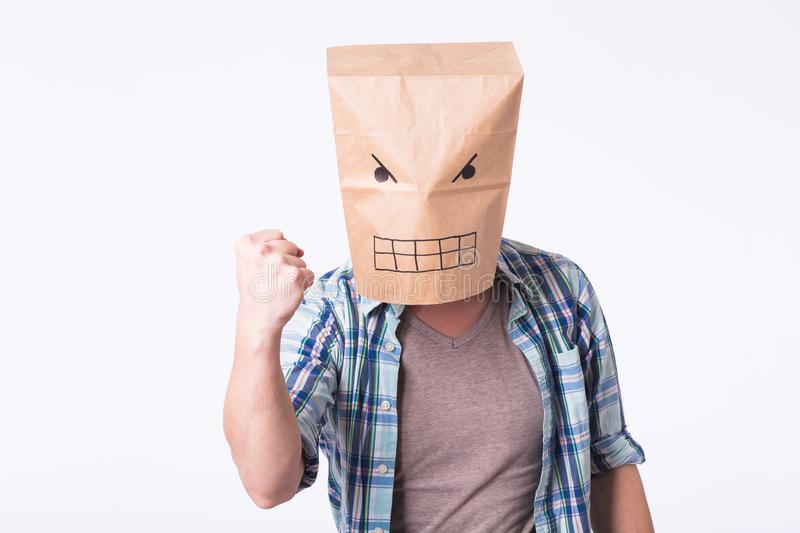 Man with cardboard box on his head and drawing of angry emoticon face. Angry man starting a fight. royalty free stock photography
