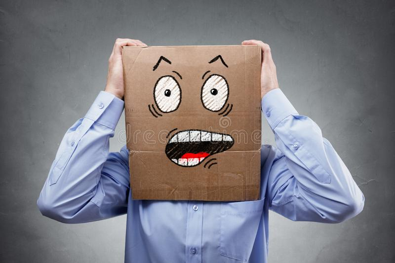 Man with cardboard box on his head showing shocked and surprised expression stock images