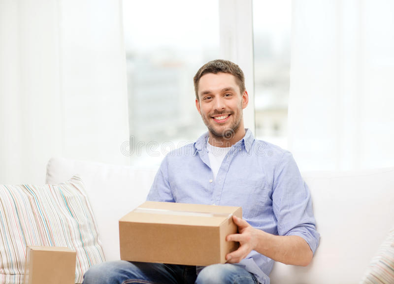 Man with cardboard boxes at home. Post, home and lifestyle concept - smiling man with cardboard boxes at home royalty free stock image