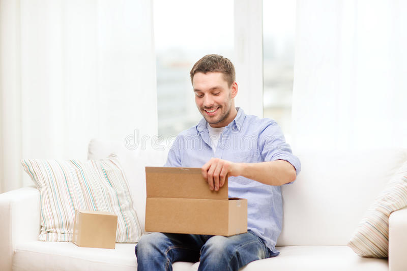Man with cardboard boxes at home. Post, home and lifestyle concept - smiling man with cardboard boxes at home royalty free stock photos
