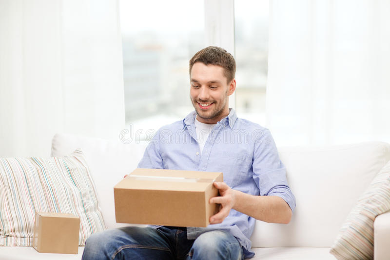 Man with cardboard boxes at home. Post, home and lifestyle concept - smiling man with cardboard boxes at home stock images
