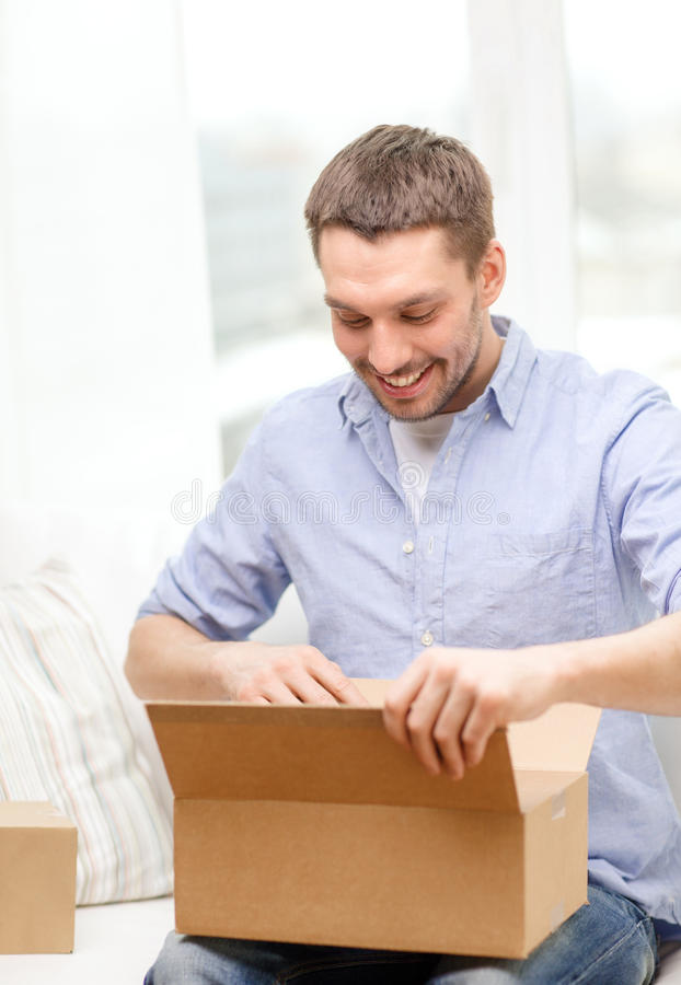 Man with cardboard boxes at home. Post, home and lifestyle concept - smiling man with cardboard boxes at home royalty free stock photography