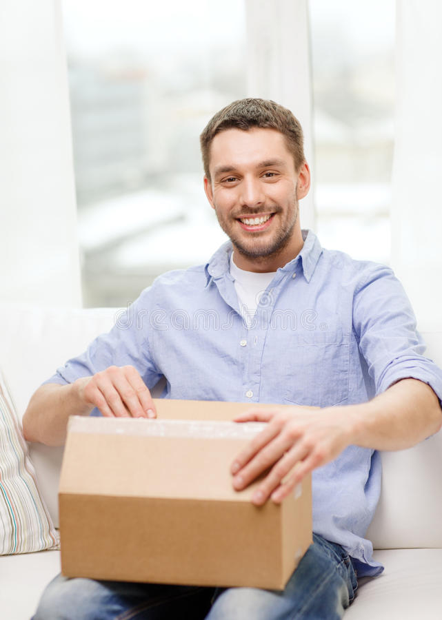 Man with cardboard boxes at home. Post, home and lifestyle concept - smiling man with cardboard boxes at home royalty free stock images