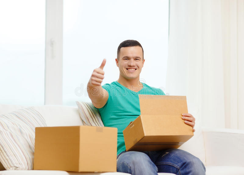 Man with cardboard boxes at home showing thumbs up. Post, home and lifestyle concept - smiling man with cardboard boxes at home showing thumbs up stock image