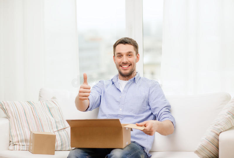 Man with cardboard boxes at home showing thumbs up. Post, home and lifestyle concept - smiling man with cardboard boxes at home showing thumbs up royalty free stock image